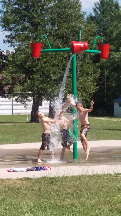 Three boys in swim trunks playing in Camp Huron mini-water park.