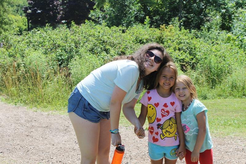 Female staff member posing with two young campers