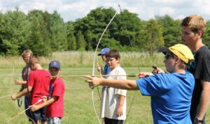 Several young campers receiving an archery lesson