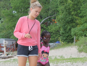 Female staff member walking near the beach with young female camper