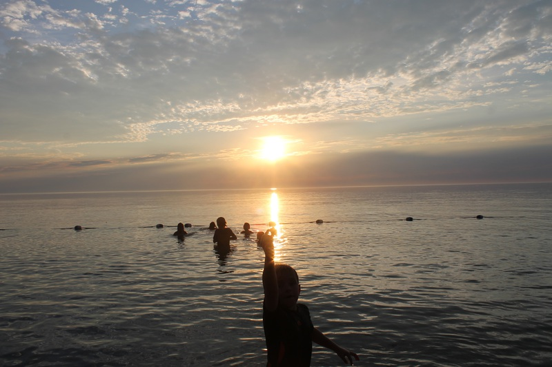 Sunset at Camp Huron showing young campers in the water