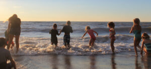 children wading into the waves of Lake Huron