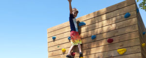 camper at the top of the climbing wall
