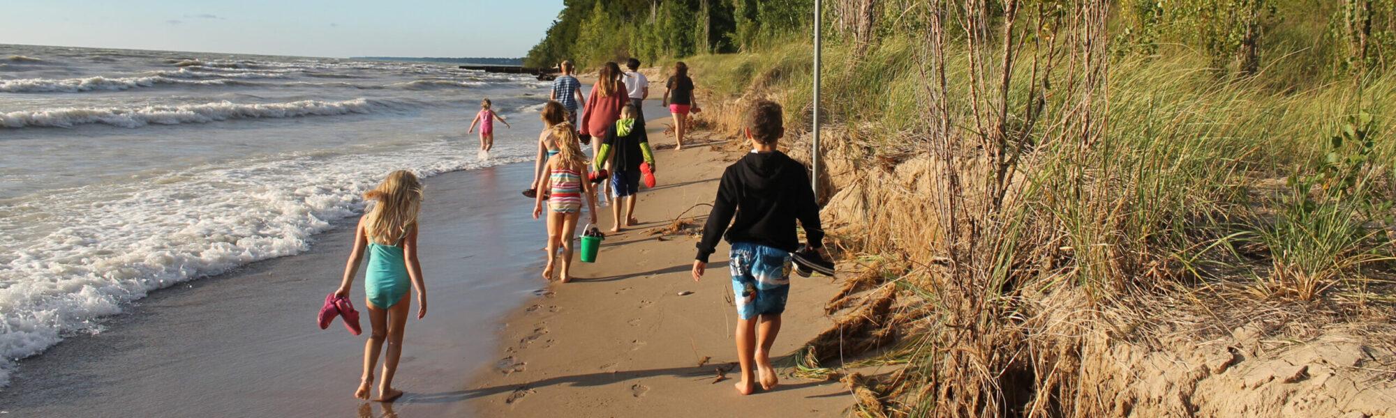 people walking on the beach of Lake Huron