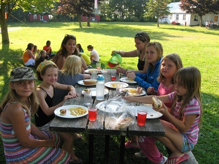 Young campers eating at a picnic table