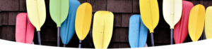 colourful paddles leaning against a cedar wall
