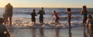 young campers wading into the waves