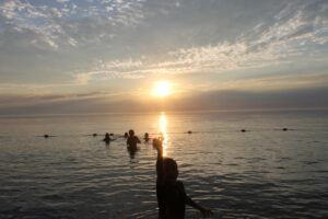 sun setting over swimmers in Lake Huron