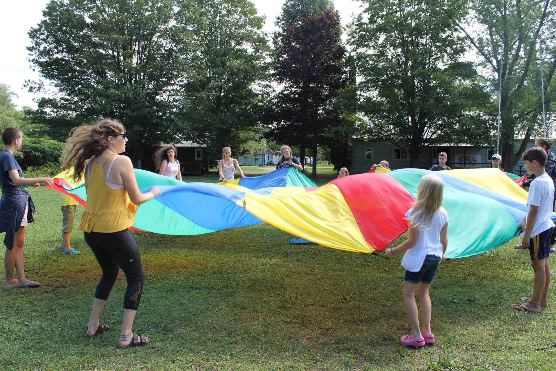 Campers playing with a colorful parachute