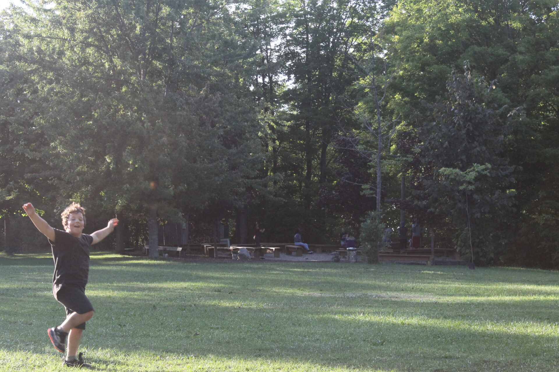 Young camper running with arms up raised