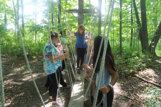 Young campers on rope bridge