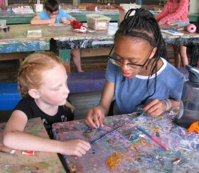 Councillor teaching young girl crafts